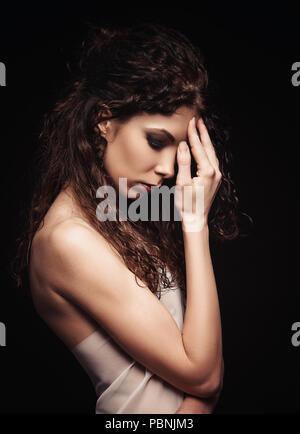 Portrait dramatique de belle jeune fille triste parmi l'obscurité Banque D'Images