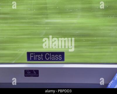 La première classe enseigne sur un train en marche avec un fond vert indiquant la vitesse de déplacement. Nord-est de l'Écosse, au Royaume-Uni. Banque D'Images