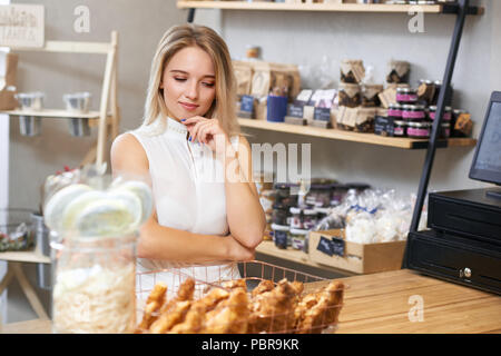 Jolie fille aux cheveux blonds choix croissants debout sur la surface en bois dans une boutique locale. Le port de blouse blanche, à la recherche, l'intéressé satisfait, souriant. Se sentir heureux. Marchandises sur arrière-plan. Banque D'Images