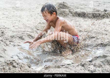 Les sauts dans le sable sale garçon Banque D'Images
