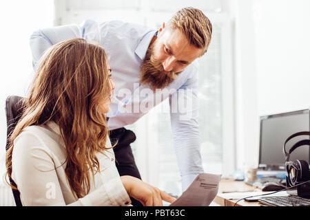 Équipe réussi: business man and woman sitting at desk parle de rapports et de finances. Banque D'Images