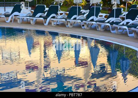 Piscine à un hôtel de villégiature. Compte tenu de soirée privée avec transats reflète dans l'eau Banque D'Images