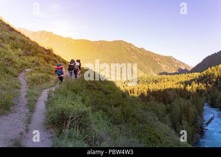 Mans randonnées au coucher du soleil des montagnes avec sac à dos lourd de vie voyage wanderlust adventure concept vacances piscine seul dans la nature Banque D'Images