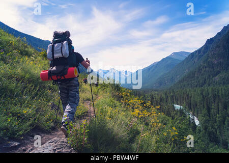 Homme randonnée au coucher du soleil des montagnes avec sac à dos lourd de vie voyage wanderlust adventure concept vacances piscine seul dans la nature. Nordic Banque D'Images