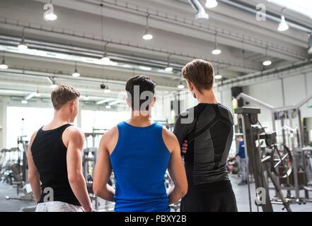 Jeunes amis de crossfit gym moderne, debout et à parler. Vue arrière. Banque D'Images