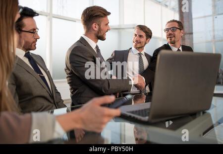 Des collègues de shaking hands in office Banque D'Images