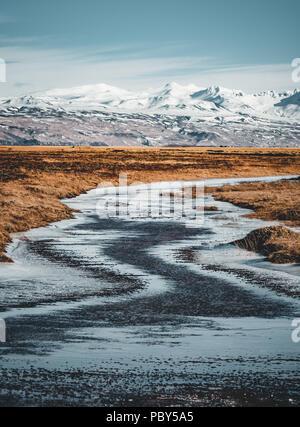 Scène d'hiver de montagne typique de l'Islande avec l'herbe en premier plan et massif montagne en arrière-plan. Banque D'Images