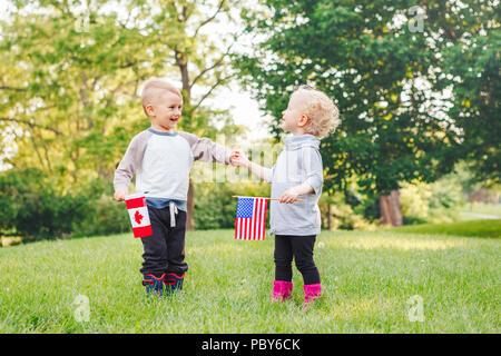 Heureux adorable petit blond Caucasian girl and boy smiling rire tenant la main et en agitant des drapeaux américains et canadiens, à l'extérieur dans le parc, la célébration de Banque D'Images