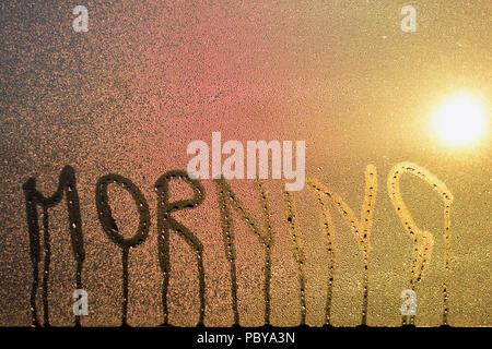 Matin écrit dans la condensation, et des gouttes, sur une fenêtre avec un soleil jaune diffusées par l'intermédiaire de l'eau Banque D'Images