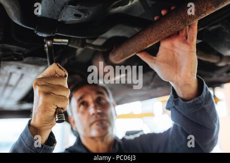 Mécanicien de voiture du serrage du tuyau d'échappement sous la voiture. Les hommes de réparation Auto réparation d'une voiture en station-service. L'accent dans la main avec passage clé réparateur Banque D'Images