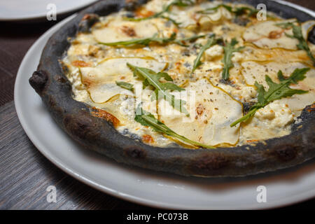 Pizza au fromage noir servi sur table in restaurant Banque D'Images