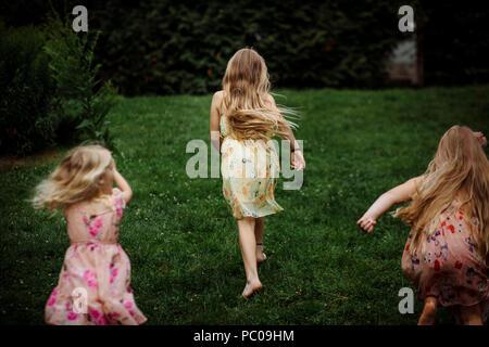 L'apparition de trois petites filles habillées en robe courir dans le parc Banque D'Images