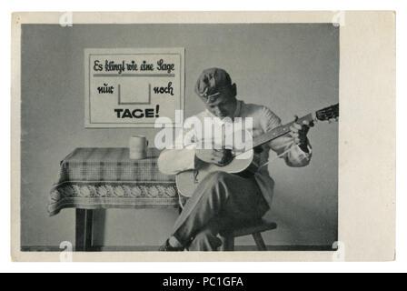 Carte postale photo historique allemand: soldat dans le fourrage joue de la guitare assis sur une chaise. L'armée en matière de loisirs, la seconde guerre mondiale, l'Allemagne, Troisième Reich
