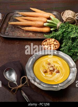 Soupe de carottes végétarien savoureux servi avec croûtons crème en étain métal bol. Botte de carottes, croûtons et cuillère sur fond marron foncé Banque D'Images