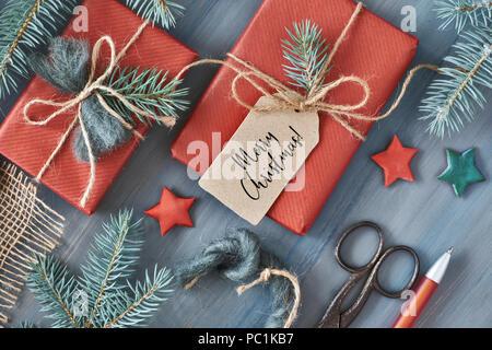 Fond en bois rustique avec des branches de sapin et des cadeaux de Noël cadeau enveloppé dans du papier rouge. Arrière-plan de saison tourné à partir de ci-dessus. Mise à plat, vue du dessus, Banque D'Images