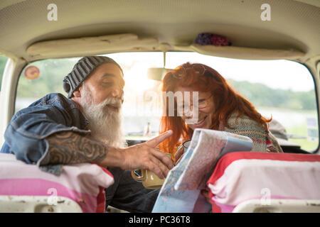 Vieux couple hipster assise dans une voiture et à la recherche à une carte routière Banque D'Images