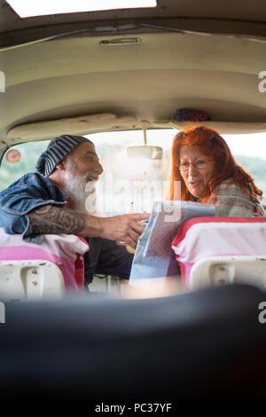 Un vieux couple hipster assis dans un camping-van, boire du café et à la recherche à une feuille de route. il est tatoué et il porte une barbe blanche, elle avait les cheveux rouges Banque D'Images