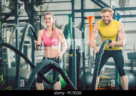 Couple solide avec l'exercice au cours de l'entraînement fonctionnel de cordes bataille Banque D'Images