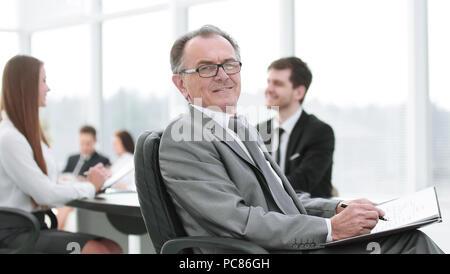 Pensive man in suit avec son équipe travailler derrière Banque D'Images