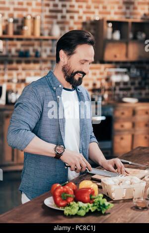 Handsome smiling barbu salade de légumes de cuisson dans la cuisine Banque D'Images