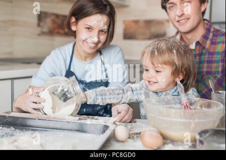 Adorable petit enfant aide ses parents à cuisiner à la cuisine Banque D'Images