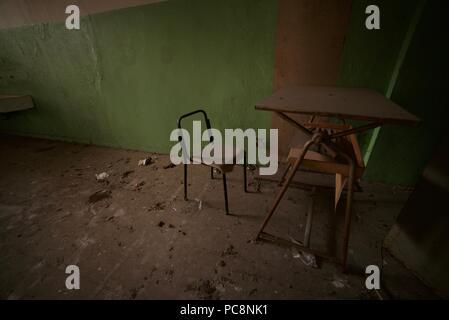 Ancienne maison victorienne bureau et chaise à l'intérieur d'une classe d'une ancienne école abandonnée Banque D'Images