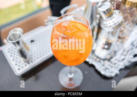 Aperol spritz cocktail dans le verre embué, selective focus. Boisson alcoolisée basé sur comptoir bar avec des cubes de glace et d'oranges. metal shakers en arrière-plan Banque D'Images