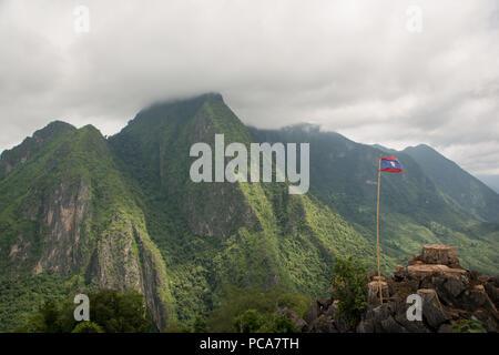 Nong Khiaw vue ci-dessus au Laos Lao PDR avec drapeau et misty montagnes luxuriantes en tbe en arrière. Banque D'Images