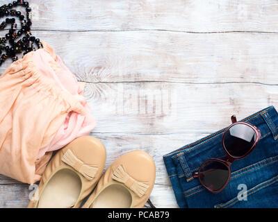 Mise à plat avec des vêtements de femme, chapeau, lunettes de soleil, collier. Les accessoires et les chaussures de l'été sur fond de bois Banque D'Images