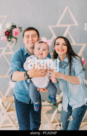 Les parents sont souriants et oscillante de jouer avec leur bébé à la maison joliment décorée.