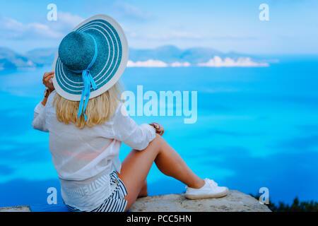 Jolie femme avec chapeau de soleil turquoise touristiques bénéficiant d'amazing azure seascape, Grèce. Cloudscape ombre sur la surface de la mer en arrière-plan. Banque D'Images