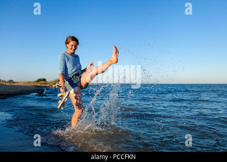 Concept de l'été vacances à la mer et vivre le style. Une jeune femme brune sourit, les promenades le long de la plage, jouer avec les vagues, les sprays autour d'un lot et en Banque D'Images