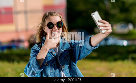 Une adolescente. L'été dans la nature. Dans ses mains est titulaire d'un smartphone. Prendre des photos de vous-même sur le téléphone. Avec un geste de mains montre super, la classe. Elle porte des vêtements jeans et lunettes de soleil. Banque D'Images