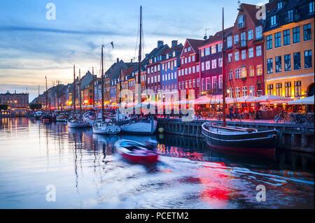 Scène en soirée avec bateaux amarrés par allumé du port de Nyhavn, Copenhague, Danemark Banque D'Images