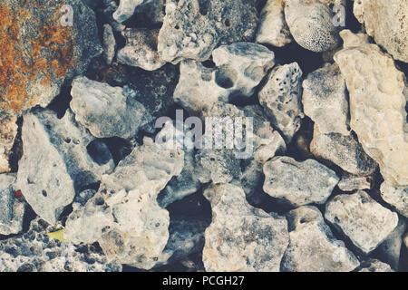 Grande énorme mer océan texturé des pierres et cailloux sur le sol, fond écran libre, tonique avec retro vintage style effet film filters Banque D'Images
