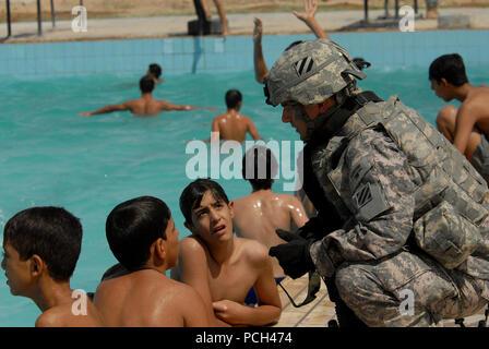Un soldat américain affecté au détachement de sécurité personnelle, 4e Bataillon, 64e régiment de blindés, 3e Division d'infanterie, parle aux garçons qu'il fournit la sécurité à l'ouverture d'une nouvelle piscine dans Risalah, Bagdad, Iraq, 18 septembre 2008.