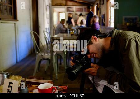 Un homme de prendre une photo dans un café, Townsville, Queensland, Australie Banque D'Images