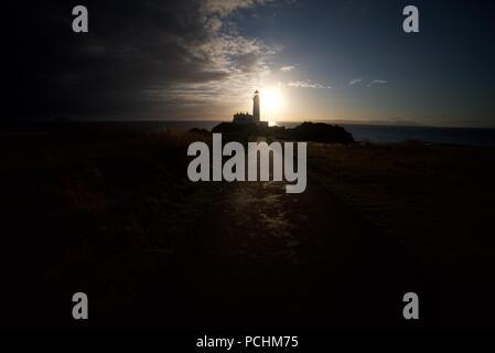 Silhouette d'un phare (Lighthouse) Turnberry le long de la Côte d'Ayrshire en regard de l'Atout Turnberry Golf, avec le coucher du soleil dans l'arrière-plan.