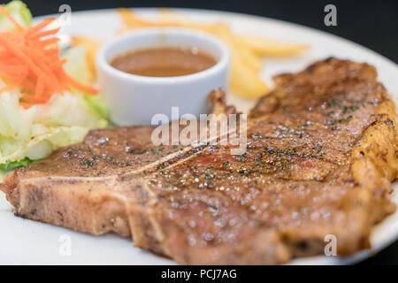 L'aloyau grillé tendre ou t-bone steak servi avec des frites dorées et salade d'herbes fraîches accompagnées de sauce ketchup poivre noir. Banque D'Images