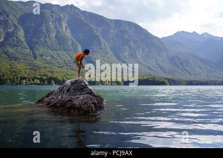 Garçon debout sur le roc de la pêche dans le lac Banque D'Images