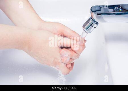 Laver les mains Savonnées sous tourné sur l'eau dans la salle de bains Banque D'Images