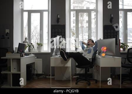 Un homme pense à une location dans un bureau moderne tout en vous relaxant