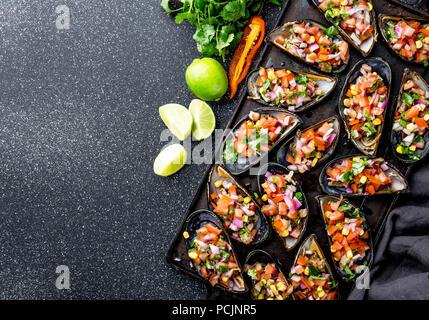 La nourriture péruvienne. Choros a la chalaca. Gros moules, choros zapatos assaisonné de purple oignon, les tomates, le maïs et le citron. Vue de dessus, fond noir. Plat péruvien traditionnel Banque D'Images