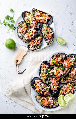 La nourriture péruvienne. Choros a la chalaca. Gros moules, choros zapatos assaisonné de purple oignon, les tomates, le maïs et le citron. Vue de dessus, fond blanc. Plat péruvien traditionnel Banque D'Images