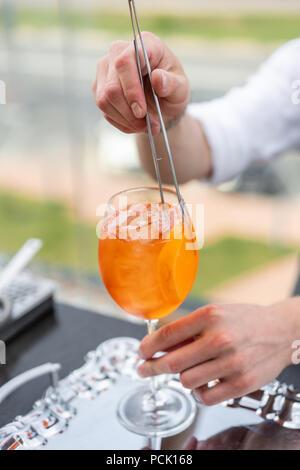 Barman cocktail Aperol spritz fait. Le verre embué, selective focus. Boisson alcoolisée basé sur comptoir bar avec des cubes de glace et d'oranges. outdoor party