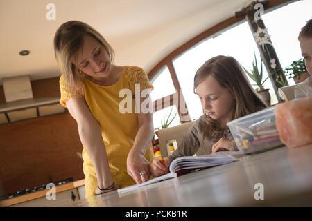 Mère d'aider les enfants à faire leurs devoirs dans la cuisine Banque D'Images