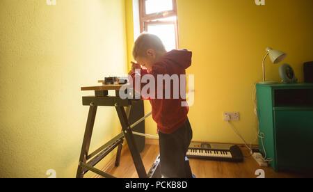 Garçon à l'aide de l'outil sur planche en bois Banque D'Images
