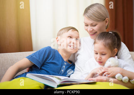 Belle mère est en train de lire un livre à ses jeunes enfants. Soeur et frère est l'écoute d'une histoire. Banque D'Images