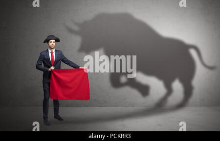 Businessman standing avec tissu rouge dans sa main et big bull ombre sur le mur Banque D'Images