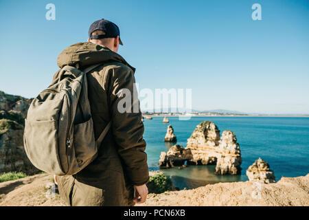 Un touriste ou voyageur avec un sac à dos admire la vue magnifique sur l'océan Atlantique et la côte près de la ville appelée Lagos au Portugal. Banque D'Images